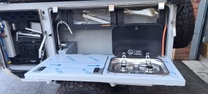 Available from TUFF-TREK UK the METALIAN MAXI DELIXE equipped with twin burner dometic gas stove, pumped water tap and comprehensive cuboards